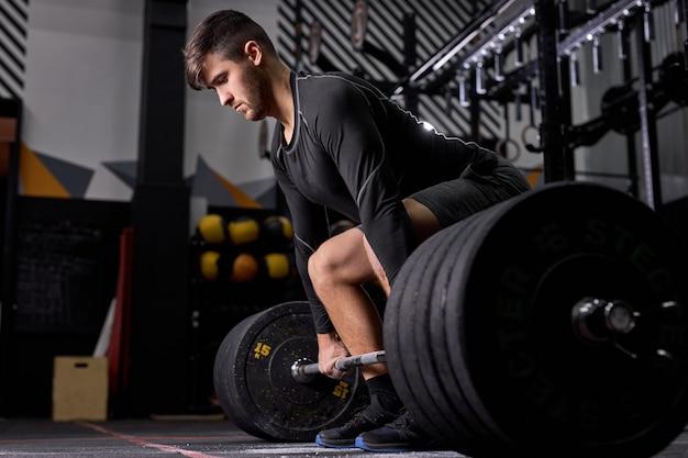 Atleta in piedi sul ginocchio che si prepara a fare stacco in palestra, giovane uomo caucasico in abiti sportivi neri impegnato nel bodybuilding, concentrato sul sollevamento pesi. sport, concetto di cross fit