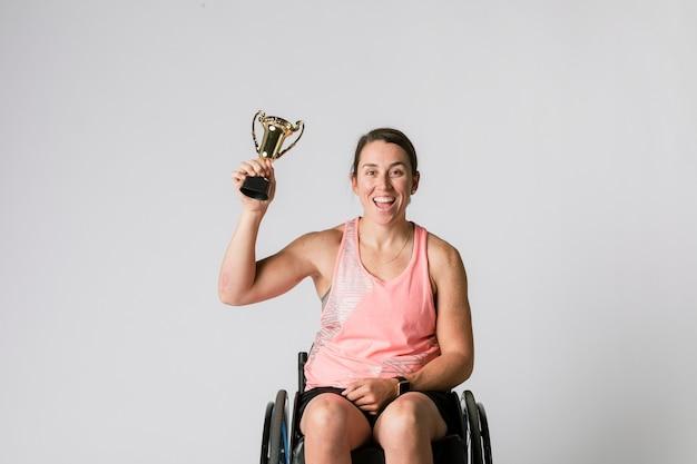 Atleta in sedia a rotelle che tiene un trofeo