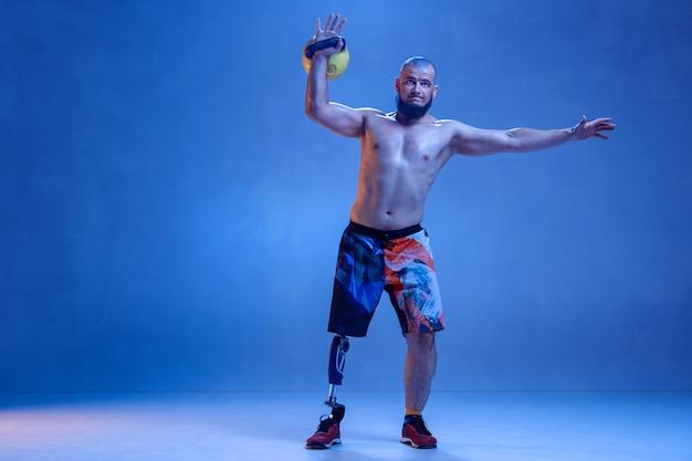 Atleta con disabilità o amputato isolato sulla parete blu dello studio