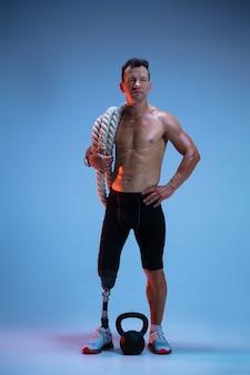 Atleta con disabilità o amputato isolato sulla parete blu sportivo professionista maschio