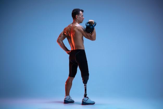 Atleta con disabilità o amputato isolato sulla parete blu