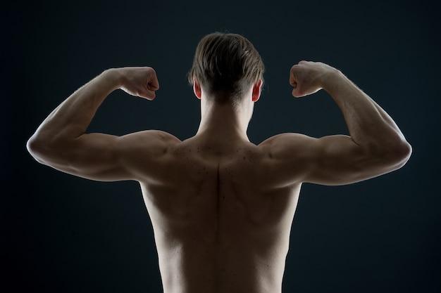Atleta con vista posteriore del busto in forma uomo bodybuilder flette i muscoli del braccio lo sportivo mostra i bicipiti