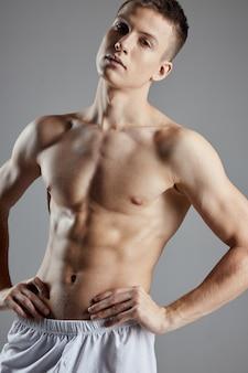 Atleta con addominali pompati mano nella mano dalla cintura su sfondo grigio vista ritagliata.