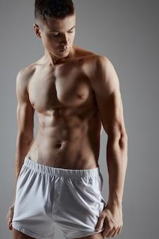 Atleta con un torso pompato in pantaloncini bianchi su un grigio