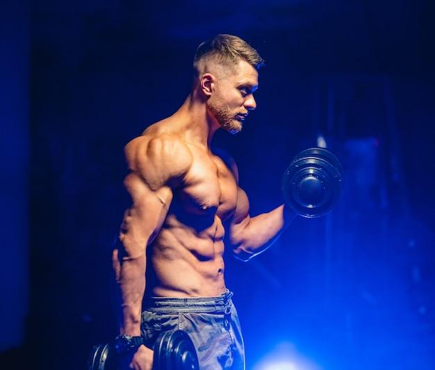Atleta con un corpo forte che fa il lavoro spingendo verso l'alto esercizio in palestra.