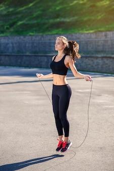 La donna dell'atleta che salta con il salto della corda allo stadio