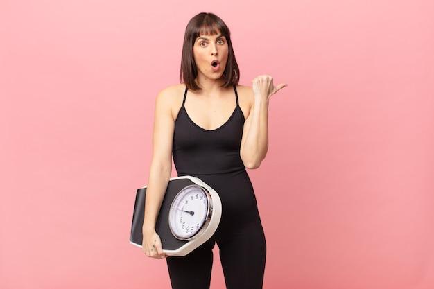 Atleta donna che sembra stupita per l'incredulità, indicando l'oggetto sul lato e dicendo wow, incredibile