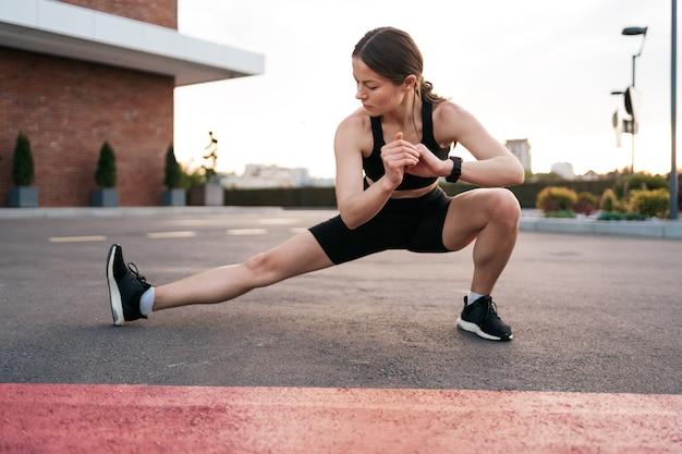 Donna atleta che si prepara per la corsa sulla strada della città. riscaldamento e allungamento delle gambe.