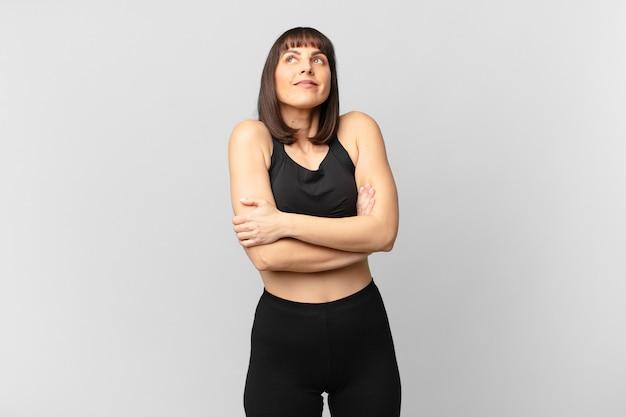 Donna atleta che alza le spalle, si sente confusa e incerta, dubitando con le braccia incrociate e lo sguardo perplesso