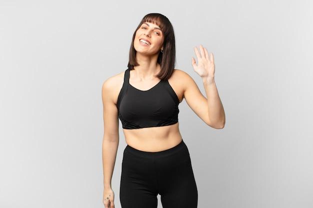 Atleta donna che sorride allegramente e allegramente, agitando la mano, accogliendoti e salutandoti, o salutandoti