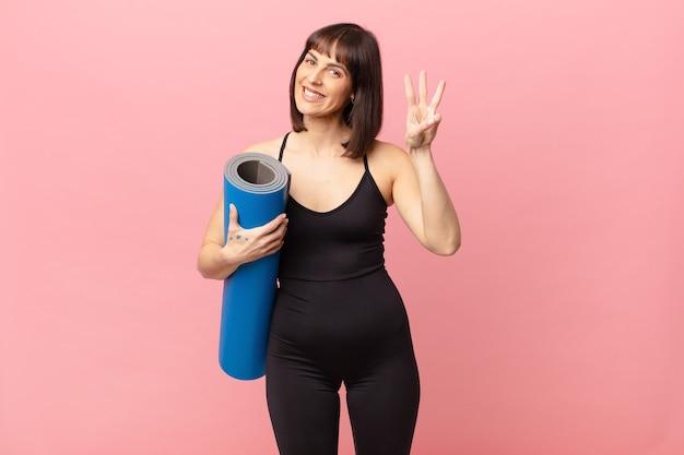 Atleta donna sorridente e dall'aspetto amichevole, mostrando il numero tre o il terzo con la mano in avanti, conto alla rovescia