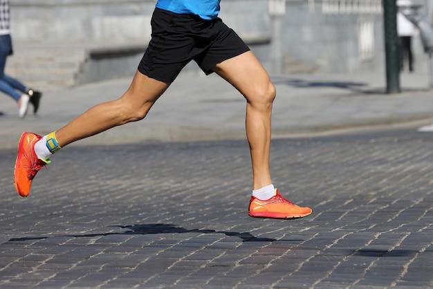 Gli atleti corrono maratone sul marciapiede