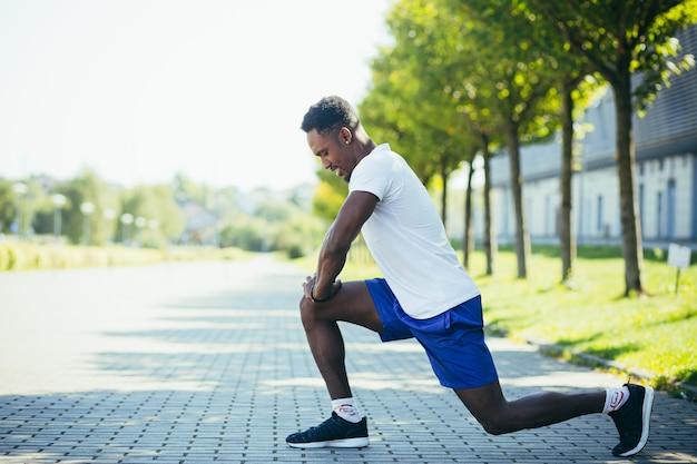 Uomo afroamericano atletico che fa allenamenti mattutini, stretching e fitness