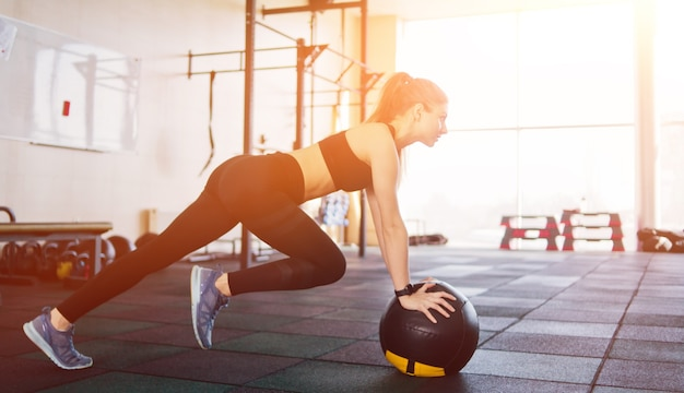 Donna attraente atletica che fa un esercizio che solleva la gamba appoggiata sulla palla medica. concetto di allenamento funzionale