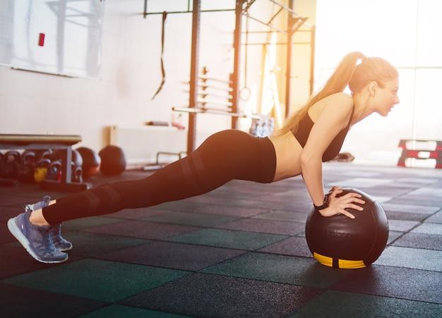Donna attraente atletica che fa spingere verso l'alto l'esercizio con la palla medica. allenamento funzionale