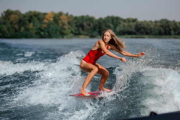 Donna bionda atletica che pratica il surfing a bordo giù l'acqua blu
