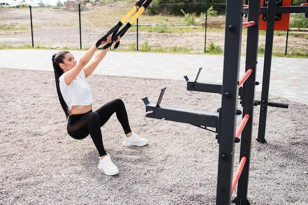 Atletica donna bruna con una maglietta bianca durante il giorno si allena con l'aiuto di cinghie per il fitness nel parco giochi