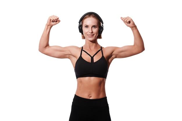 La sportiva caucasica atletica mostra il suo forte braccio muscoloso e ascolta musica su sfondo bianco isolato
