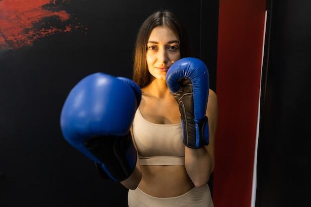 Ragazza atletica in posa di guantoni da boxe blu