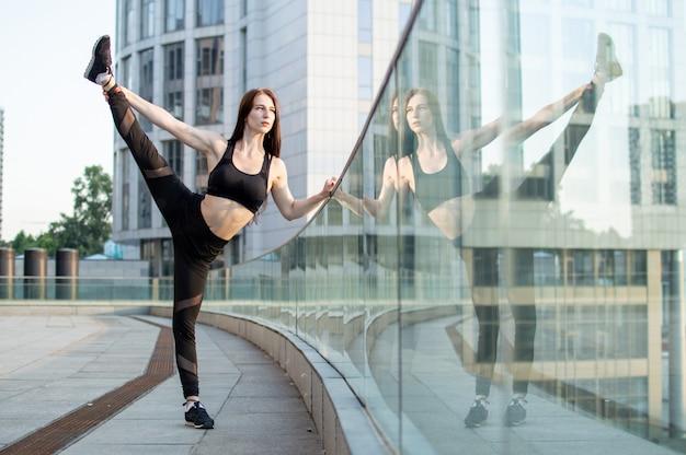 Ragazza atletica impegnata in atletica leggera sullo sfondo della città, si allena al mattino per strada, una donna fa stretching e trucchi di ginnastica