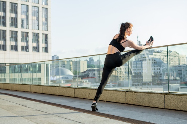 Ragazza atletica impegnata in atletica leggera in città, si allena al mattino per strada, una donna fa stretching e trucchi di ginnastica