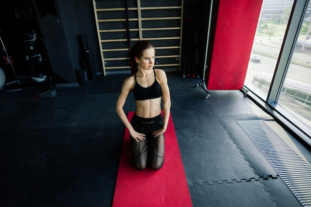 Ragazza atletica in abiti sportivi esegue esercizi con un bilanciere, manubri. fitness, allenamento, stile di vita sano
