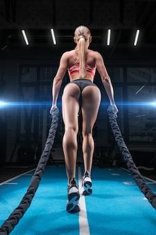 Ragazza atletica si allena in palestra con corde speciali. vista posteriore.