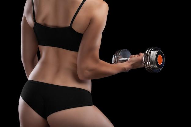 Ragazza atletica con manubri in mano isolato sul nero.