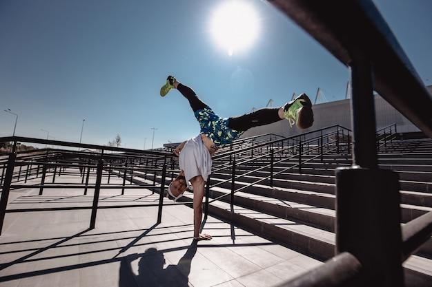Ragazzo atletico con fascia in testa vestito con maglietta bianca, leggings neri e pantaloncini blu sta facendo il trucco in piedi su una mano sulle scale accanto alla ringhiera fuori in una giornata di sole.
