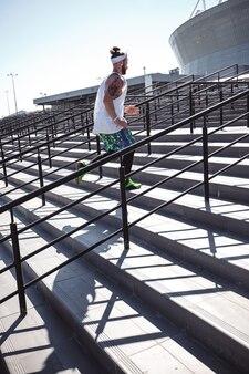 Ragazzo atletico con fascia in testa vestito con maglietta bianca, leggings neri e pantaloncini blu sta correndo su per le scale fuori in una giornata di sole.