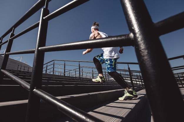 Ragazzo atletico con fascia in testa vestito con maglietta bianca, leggings neri e pantaloncini blu sta correndo su per le scale con ringhiere nere fuori in una giornata di sole. .