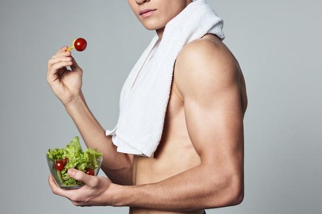 Culturista uomo atletico mangiare sano piatto insalata di close-up