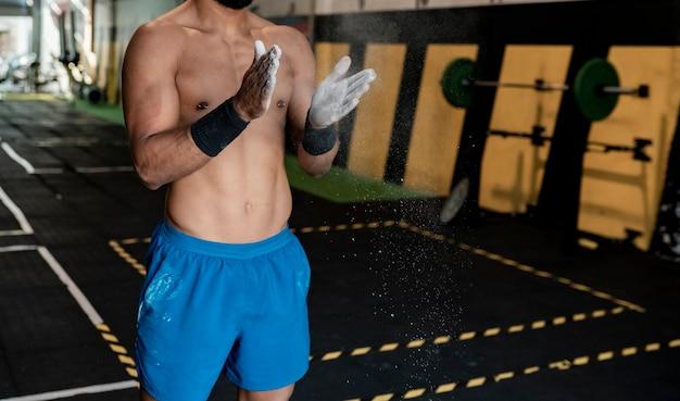 Uomo atletico in palestra con le mani di magnesio