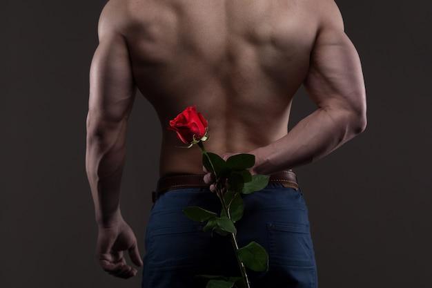 Uomo atletico che tiene una rosa rossa dietro la schiena. concetto di relazioni d'amore e romanticismo
