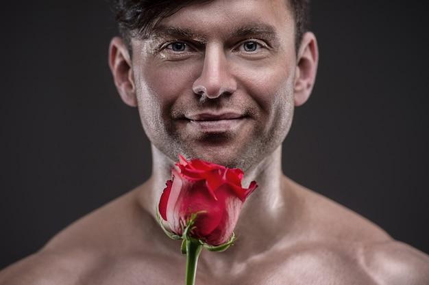 Uomo atletico che tiene in mano una rosa rossa. concetto di relazioni d'amore e romanticismo