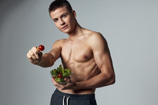 Uomo atletico torso muscolare piatto insalata cibo sano sfondo isolato