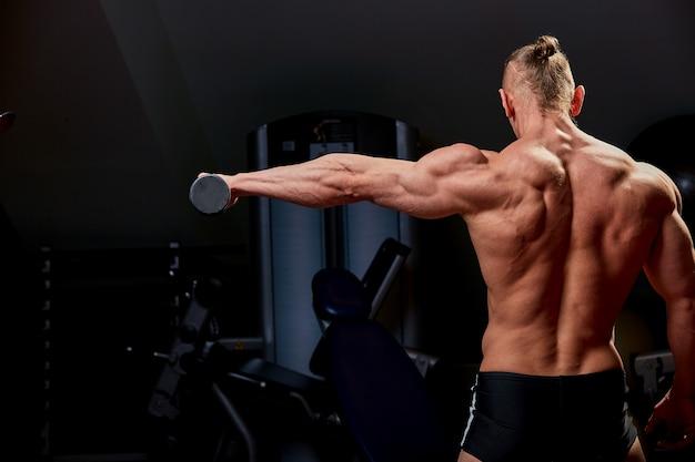 Posa atletica dell'uomo. foto dell'uomo con fisico perfetto sulla parete nera. vista posteriore. forza e motivazione