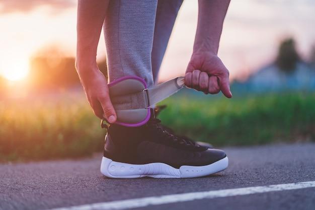 L'uomo atletico mette su pesi sportivi per camminare durante l'allenamento all'aperto. stile di vita sano e sportivo.