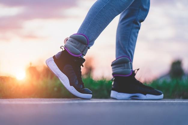 Uomo atletico cammina con pesi sportivi per rafforzare i muscoli e la resistenza durante l'allenamento all'aperto. stile di vita sano e sportivo.