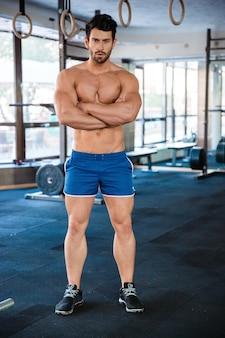 Uomo atletico che indossa pantaloncini blu in piedi con le braccia incrociate
