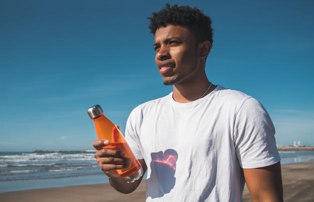 Uomo atletico con una bottiglia di acqua