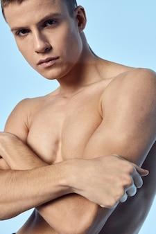 Uomo atletico con bodybuilder di corpo muscoloso torso nudo braccia piegate. foto di alta qualità