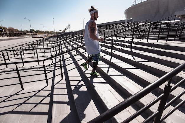 L'uomo atletico con la fascia in testa vestito con maglietta bianca, leggings neri e pantaloncini blu sta salendo le scale fuori in una giornata di sole.