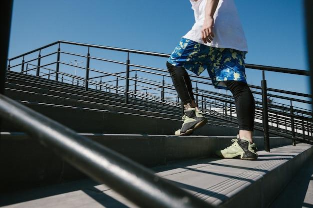 Uomo atletico con fascia in testa vestito con maglietta bianca, leggings neri e pantaloncini blu sta salendo le scale con ringhiere nere fuori in una giornata di sole.