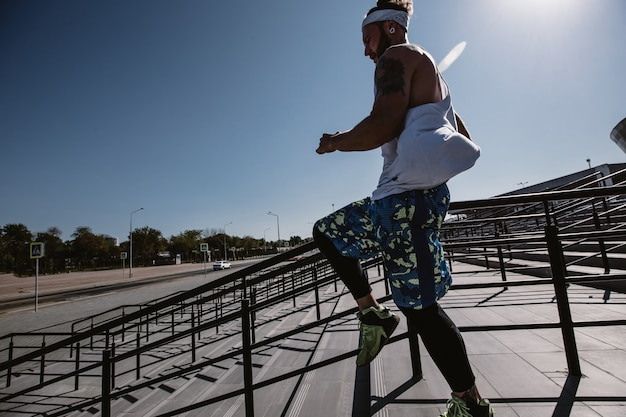 Uomo atletico con fascia in testa vestito con maglietta bianca, leggings neri e pantaloncini blu sta correndo giù per le scale fuori in una giornata di sole.