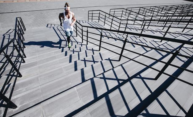 L'uomo atletico con la fascia in testa vestito con maglietta bianca, leggings neri e pantaloncini blu sta correndo su per le scale fuori in una giornata di sole.