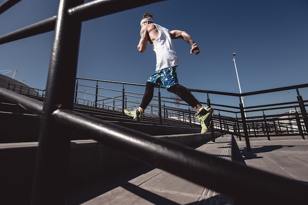 Uomo atletico con fascia in testa vestito con maglietta bianca, leggings neri e pantaloncini blu sta correndo su per le scale con ringhiere nere fuori in una giornata di sole.
