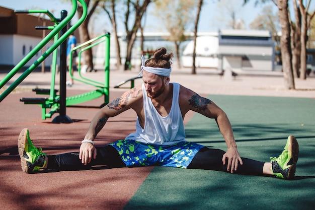 Uomo atletico con fascia in testa e tatuaggi vestito con t-shirt bianca, leggings neri e pantaloncini blu sta facendo stretching sul campo sportivo all'esterno in una giornata di sole.