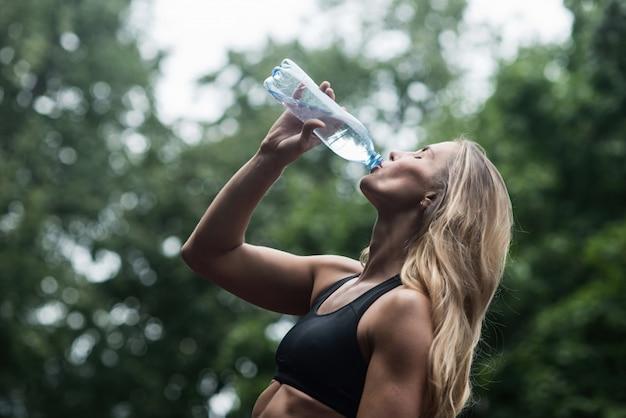 Acqua potabile della ragazza muscolare atletica dopo l'allenamento il concetto di uno stile di vita sano