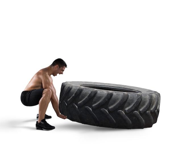 L'uomo muscoloso atletico solleva un grande pneumatico